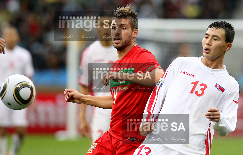 CAPE TOWN, SOUTH AFRICA, MONDAY 21 June 2010, Miguel Veloso challenges PAK Choi Jin during the match between Portugal and Korea PRK held at the new Cape Town Stadium in Green Point during the 2010 FIFA World Cup..Photo by Roger Sedres/Image SA