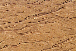 rivulets in beach sand from ocean tide