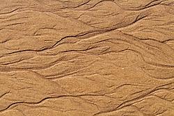 rivulets in beach sand from ocean tide