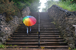 Woman with colourful umbrella climbs steps at Calton Hill on rainy day, Edinburgh, Scotland, UK