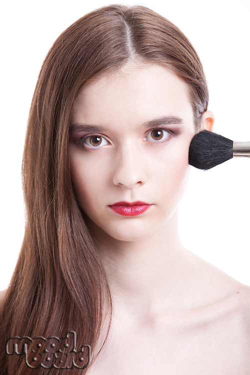 Portrait of beautiful young woman with red lips applying makeup against white background