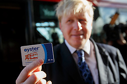 © licensed to London News Pictures. London, UK 27/01/2014. The Mayor of London, Boris Johnson shows his Oyster card whilst launching the Year of the Bus from a specially painted silver New Routemaster bus at a photocall outside the City Hall. Photo credit: Tolga Akmen/LNP