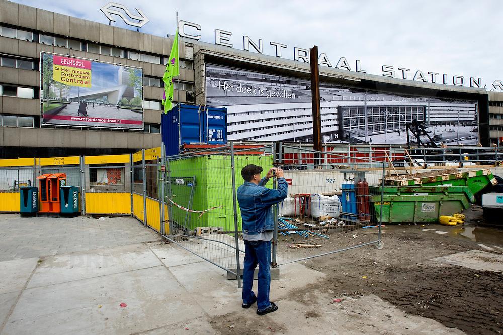 """Nederland Rotterdam 3 september 2007 20070903 .Voorbijganger/ man fotografeert het voormalige centraal station, wat op het punt staat gesloopt te worden. Op de gevel van het oude (vertrouwde) pand hangt het doek """" Het doek is gevallen """" Binnenkort zal het pand het definitief gesloopt worden.  ."""" Het doek is gevallen """" Zondag 2 september is het doek letterlijk doek gevallen voor het in 1957 geopende gebouw. Over enkele weken wordt de schepping van architect Sybold van Ravesteyn gesloopt en komt op het Stationsplein een nieuwe OV-terminal, die na 2011 ruim 300.000 reizigers per dag moet kunnen verwerken. Voorbijgangers maken een foto van het oude bekende centraal station, dat sinds 1957 dienst heeft gedaan. Een gloednieuw station zal op deze plek verrijzen. Op de achetrgrond links het tijdelijke centraal station. ..Het tijdelijke station dat de periode overbrugt tussen de sloop van het oude Rotterdam CS en de bouw van een nieuw station, kost 12 miljoen euro. Dat is een schijntje vergeleken met het half miljard waarop het nieuwe is begroot. De bedoeling is dat de tijdelijke bebouwing in februari klaar is. Het blijft open tot 2010. Het oude gebouw maakt plaats voor vijf tijdelijke. Daarvan zijn er vier voor de reizigers en een voor het personeel van de Spoorwegpolitie. ..Tijdelijk Rotterdam Centraal.1 september 2007..Alle treinreizigers opgelet! Vanaf 2 september sta je voor een dichte deur als je bij Rotterdam Centraal op de trein wilt stappen. Tenzij je de ingang van het tijdelijke Rotterdam Centraal al gevonden hebt. ..Naast het oude vertrouwde station staat al een tijdje een groot blauw gebouw en vanaf 2 september kun je daar op je trein stappen. Je kunt er zelfs een kopje koffie halen, of kleine boodschappen doen. Alle winkels zijn namelijk gewoon verplaatst naar het grootste tijdelijke station van Nederland...Het Centraal Station was al een hele tijd een grote bouwput, want er wordt heel hard gewerkt aan een nieuw, beter en vooral moderner station. Maar omdat afsc"""