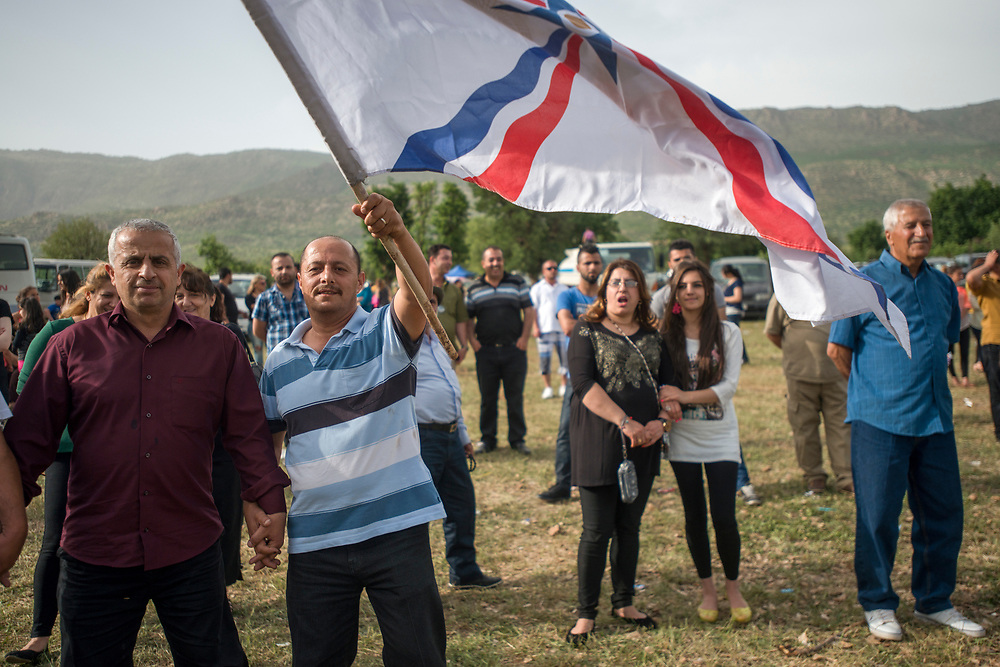 A man waves an Assyrian flag at a gathering of Iraqi Christian families in the mountains near Duhok. On Fridays in the mild Spring months throughout Kurdistan families go to the countryside to picnic, dance and socialize. Bamarne, Iraq. 09/05/2014