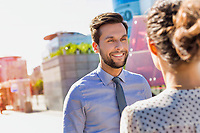Portrait of young attractive businessman smiling while talking to businesswoman