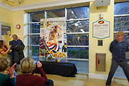 Garden City, New York, USA. March 9, 2019.  Audience applauds when, left of mural, DARIEN WARD the Baldwin Civic Association President, and at far right, MICHAEL WHITE the artist who painted mural of closeup of Nunley's Carousel horse, finished removing cover from mural during Unveiling Ceremony. Event was held at historic Nunley's Carousel in its Pavilion on Museum Row on Long Island.