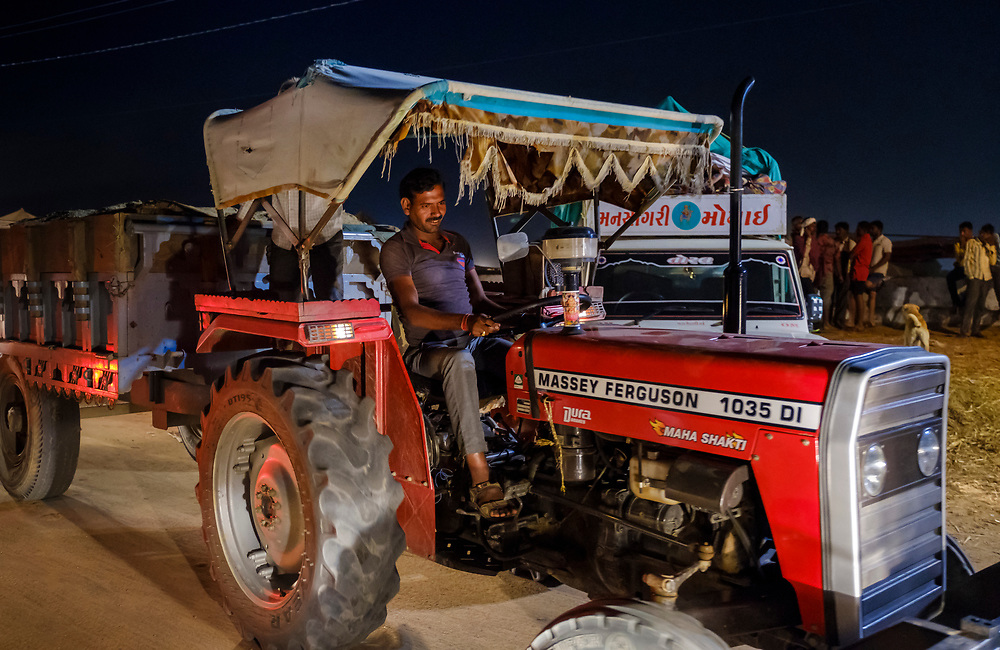 PUSHKAR, INDIA - CIRCA NOVEMBER 2016:  Man driving a tractor at night during the Pushkar Camel Fair. It is one of the world's largest camel fairs. Apart from the buying and selling of livestock, it has become an important tourist attraction.