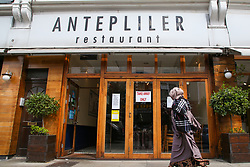 "© Licensed to London News Pictures. 24/05/2020. London, UK. A Muslim woman walks past ''ANTEPLILER' a Turkish restaurant on Green Lanes, Haringey in north London which is open for take away only due to coronavirus lockdown, as Muslims celebrate Eid al-Fitr. On Eid al-Fitr also known as ""Festival of Breaking the Fast"", a religious holiday celebrated by Muslims worldwide that marks the end of the month-long fasting of Ramadan, restaurants would normally be packed with people celebrating Eid. Photo credit: Dinendra Haria/LNP"