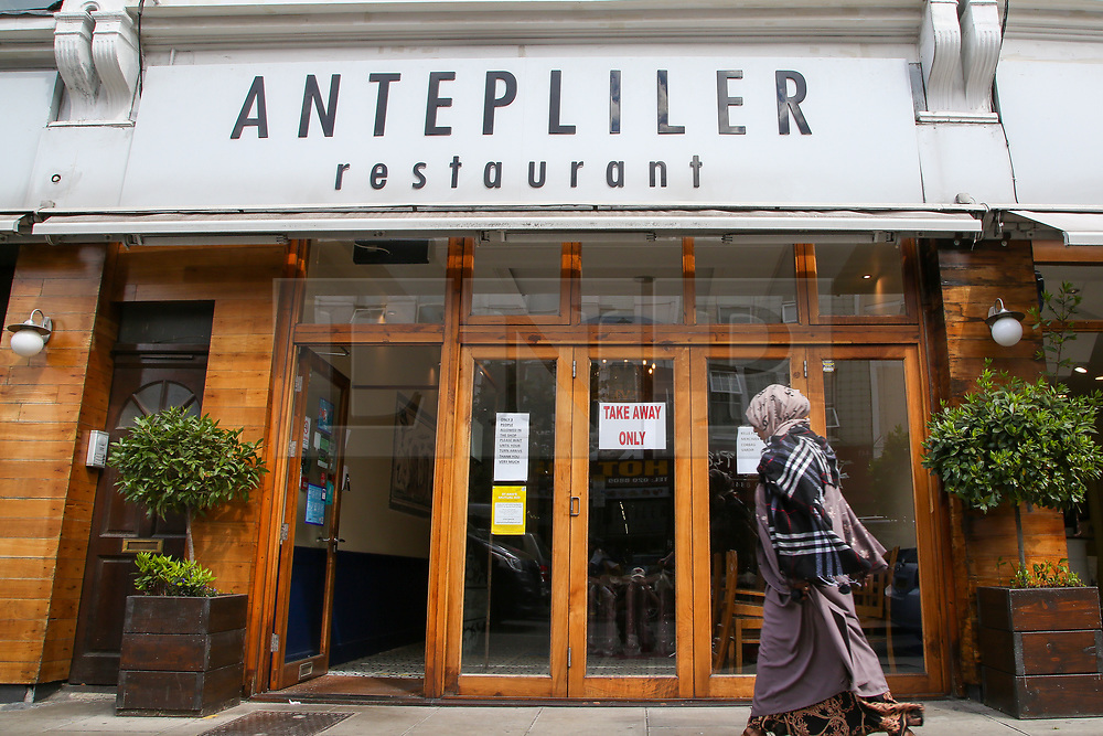 """© Licensed to London News Pictures. 24/05/2020. London, UK. A Muslim woman walks past ''ANTEPLILER' a Turkish restaurant on Green Lanes, Haringey in north London which is open for take away only due to coronavirus lockdown, as Muslims celebrate Eid al-Fitr. On Eid al-Fitr also known as """"Festival of Breaking the Fast"""", a religious holiday celebrated by Muslims worldwide that marks the end of the month-long fasting of Ramadan, restaurants would normally be packed with people celebrating Eid. Photo credit: Dinendra Haria/LNP"""