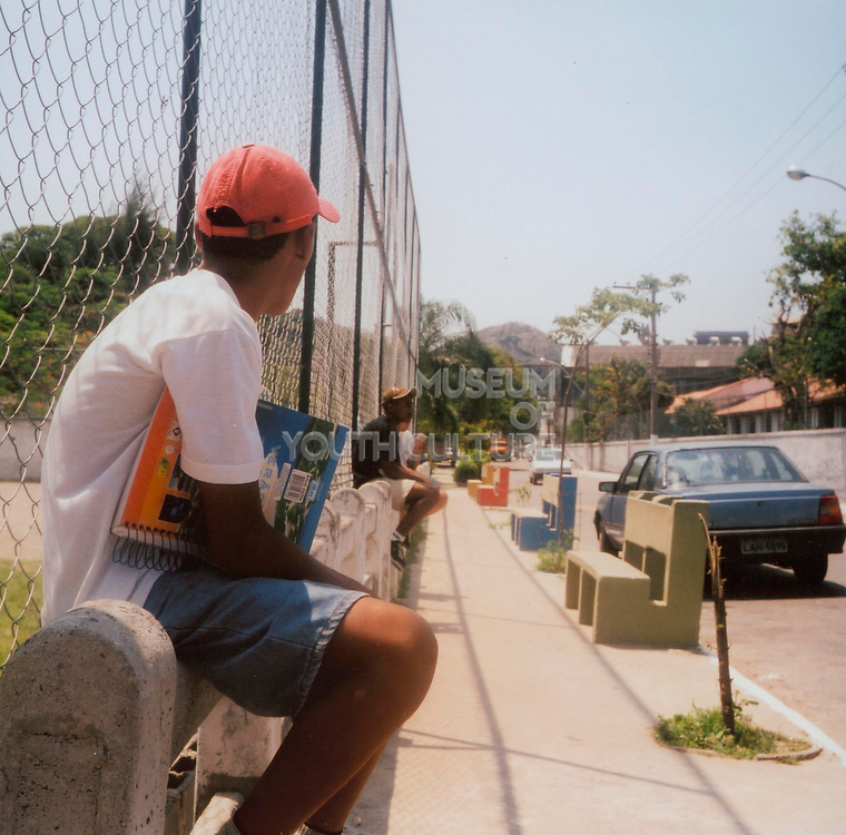 Teenage boys sitting on a concrete fence waiting for a bus holding schoolbooks Brazil