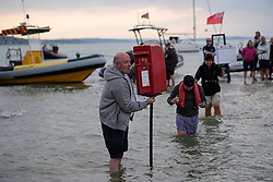 © Licensed to London News Pictures. 18/09/2016. Portsmouth, UK. A royal mail post box being erected in the sea. Teams take part in the  Bramble Bank Cricket Match in the middle of The Solent strait on September 18, 2016. The annual cricket match between the Royal Southern Yacht Club and The Island Sailing Club, takes place on a sandbank which appears for 30 minutes at lowest tide. The game lasts until the tide returns. Photo credit: Ben Cawthra/LNP