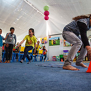 "Playing games in the Mercy Corps child friendly space ""Tom and Jerry"" helps the children acclimate to their new environment and heal from trauma. Azraq camp for Syrian refugees, Jordan, June 2014."