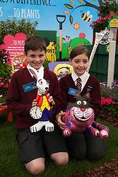 © Licensed to London News Pictures. 19/05/2014. London, England. Jack and Freya (both 10) from the Holtspur School near Beaconsfield with the White Rabbit and the Cheshire Cat which their school designed for the Miracle Gro'wers Discovery and Learning Garden.  Press Day at the RHS Chelsea Flower Show. On Tuesday, 20 May 2014 the flower show will open its doors to the public.  Photo credit: Bettina Strenske/LNP