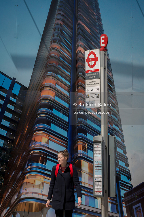 A young woman beneath a construction hoarding showing the Foster-designed Principal Tower that's under construction on Shoreditch High Street, on 10th May 2017, in London, England.