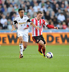 Swansea City's Neil Taylor battles for the ball with Sunderland's Craig Gardner - Photo mandatory by-line: Alex James/JMP - Tel: Mobile: 07966 386802 19/10/2013 - SPORT - FOOTBALL - Liberty Stadium - Swansea - Swansea City v Sunderland - Barclays Premier League