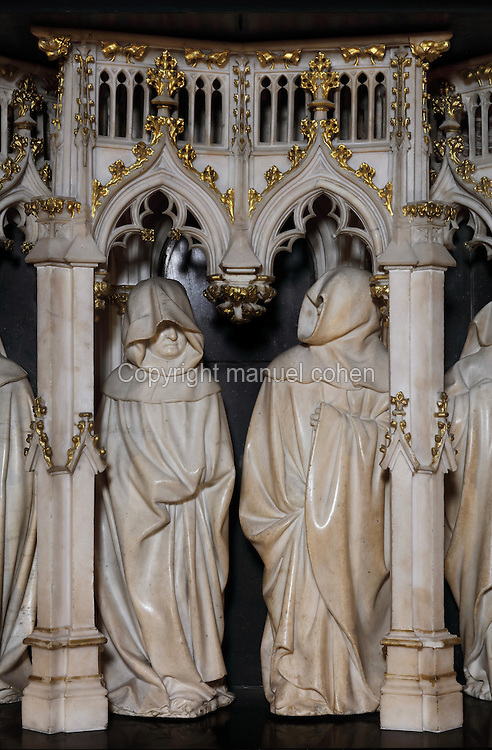 Sculptures of hooded weepers under Gothic canopies by Claus Sluter, 1340-1405, and Claus de Werve, 1380-1459, on the tomb of Philippe le Hardi, or Philip the Bold, 1342-1404, (Philippe II, duc de Bourgogne, or Philip II, Duke of Burgundy), 1381-1410, in the Grande Salle du Palais des ducs de Bourgogne, or Salle des Gardes, a 15th century Flamboyant Gothic hall, in the Musee des Beaux-Arts de Dijon, opened 1787 in the Palace of the Dukes of Burgundy in Dijon, Burgundy, France. The tomb consists of a painted alabaster effigy with lion and angels, and below, figures of pleurants or weepers among Gothic tracery. Claus Sluter worked on the weepers 1389-1404 and produced startlingly realistic sculptures, and Claus de Werve completed them 1404-10. The tombs were originally from the Chartreuse de Champmol, or Chartreuse de la Sainte-Trinite de Champmol, a Carthusian monastery which was sacked in the French Revolution and the tombs moved to Dijon cathedral then here in 1827. Picture by Manuel Cohen