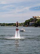 "A man ""flies"" on a flyboard on Lake Mendota, in front of the Memorial Union, University of Wisconsin-Madison."