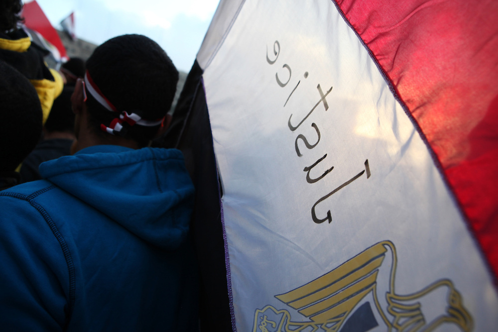 A pro-democracy protester carries an Egyptian flag at Tahrir Square.