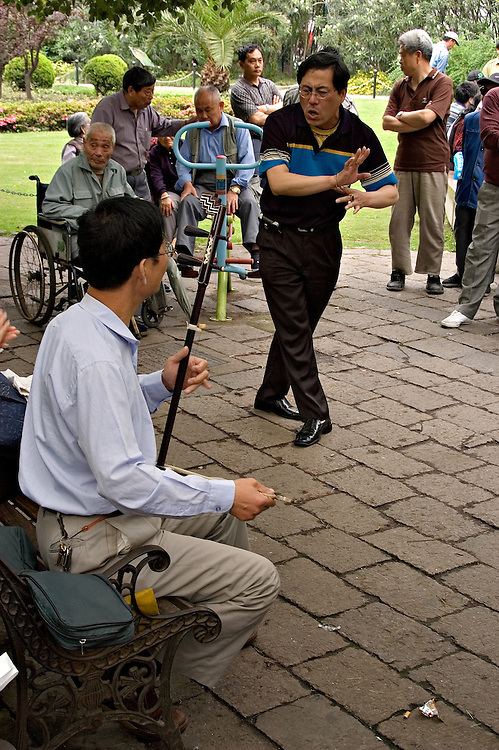 A group of men in the park put on a spontaneous performance of traditional chinese music and dance.