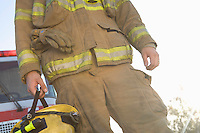 Fire fighter holding helmet