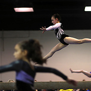 A young gymnasts performs on the uneven bars, (right), as another competitor performs on the balance beam, (centre) and the vault, (left), during competition at the 21st American Invitational 2014 competition at the XL Centre. Hartford, Connecticut, USA. USA. 31st January 2014. Photo Tim Clayton