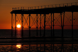 © Licensed to London News Pictures.12/06/15<br /> Saltburn by the Sea, England<br /> <br /> The rising sun can be seen through the legs of the pier as dawn breaks over Saltburn by the Sea.<br /> <br /> Photo credit : Ian Forsyth/LNP