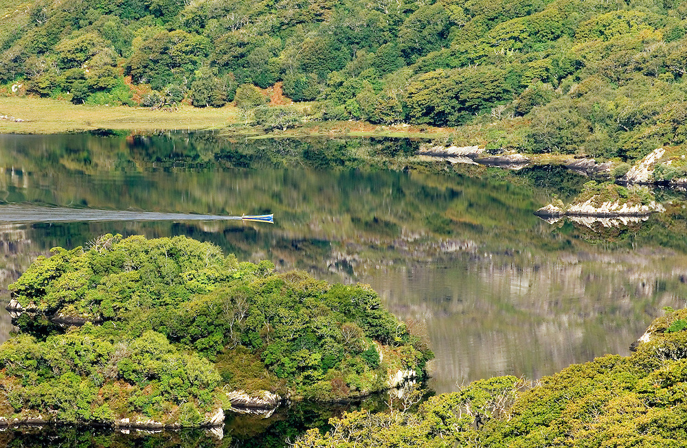 Man in small fishing boat travelling on Upper Lake, Killarney National Park, County Kerry, Ireland.