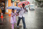 15 DECEMBER 2012 - SINGAPORE, SINGAPORE:  A man and his daughter  run through the rain with umbrellas in the Little India section of Singapore. PHOTO BY JACK KURTZ