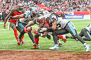 Tampa Bay Buccaneers Running Back Ronald Jones (27) dives between Carolina Panthers Defensive Back Tre Boston (33) and Carolina Panthers Linebacker Bruce Irvin (55) to touchdown during the International Series match between Tampa Bay Buccaneers and Carolina Panthers at Tottenham Hotspur Stadium, London, United Kingdom on 13 October 2019.