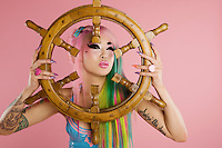 Young woman holding ship's wheel in front of her face