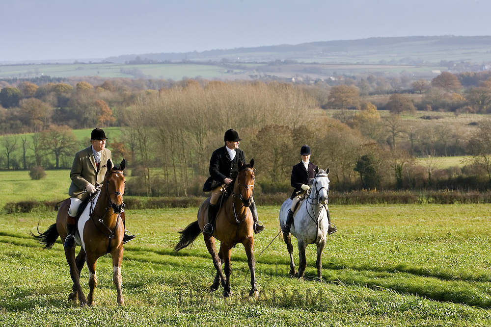 Members of Heythrop Hunt ride across field at Westcote, The Cotswolds, Oxfordshire, United Kingdom