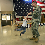 A National Guardsman swings his daughter before a sendoff celebration in Boone, Iowa in 2007. His unit was being deployed to Iraq for one year.