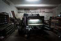 The main room of Daha Printing Press, a sweltering cellar beneath the former Las Vegas Bar, where decades of ink and sweat have spilled on the dark concrete floor.  A massive Heidelberg Original Cylinder press takes up most of the space.
