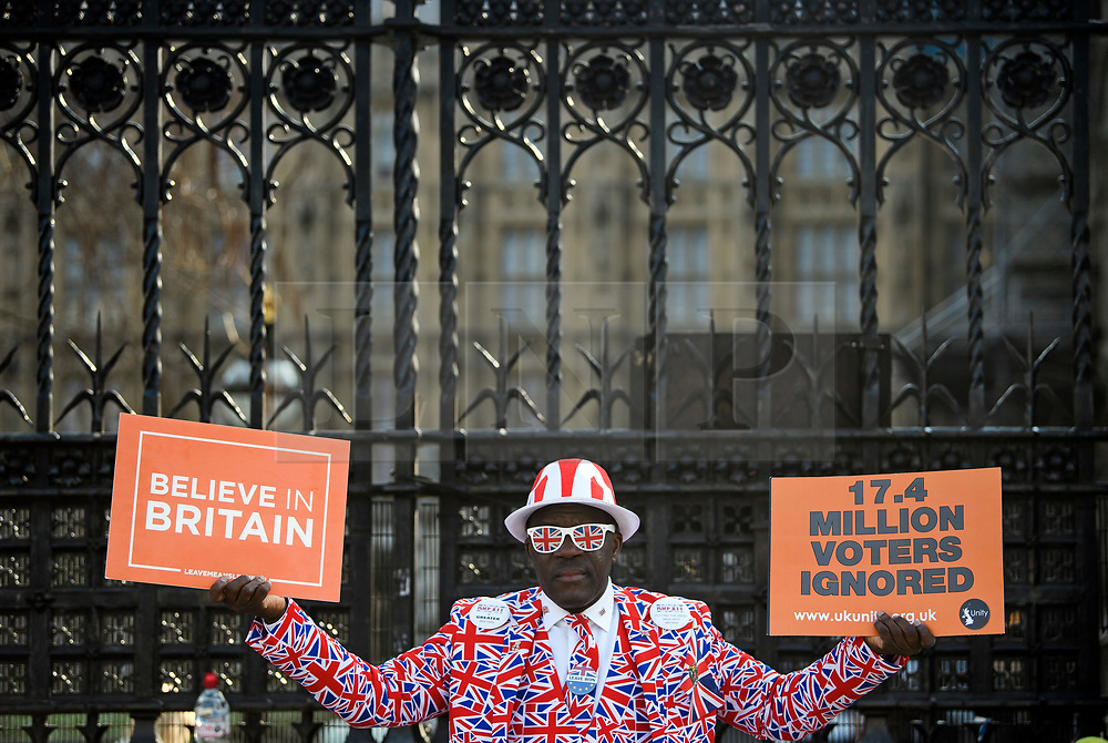 © Licensed to London News Pictures. 29/03/2019. London, UK. A pro Brexit campaigner holds up banners outside Parliament in Westminster, London. MPs will later vote on the withdrawal agreement, which sets out the terms of the UK's departure from the EU. Photo credit: Ben Cawthra/LNP