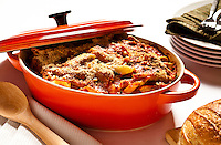 A pot of baked ziti on a table with bread, plates and silverware.