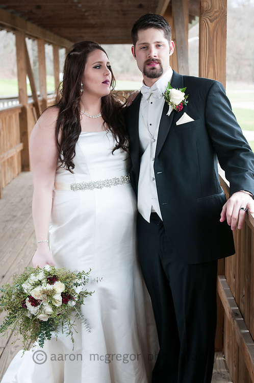Relaxed newlyweds pose on a convered bridge in Manor Park PA