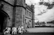 A group of older people sit in chairs waiting outside Leeds Castle, England.