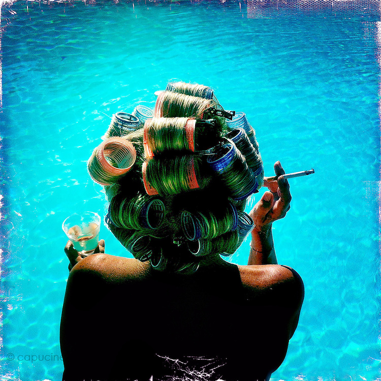 French Riviera. France. August 9th 2012..A woman relax around her swimming pool.
