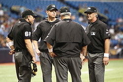 August 19, 2017 - St. Petersburg, Florida, U.S. - WILL VRAGOVIC   |   Times.Wearing white armbands, umpire Chris Guccione (68), left, Carlos Torres (37)(not wearing armband), center facing, Dana DeMuth (32) center right, and Paul Nauert (39) talk before the start of the game between the Seattle Mariners and the Tampa Bay Rays at Tropicana Field in St. Petersburg, Fla. on Saturday, Aug. 19, 2017. The World Umpires Association announced that umpires will be wearing white wristbands during all games to protest escalating verbal attacks on umpires and their strong objection to the Office of the Commissioner's response to the attacks. (Credit Image: © Will Vragovic/Tampa Bay Times via ZUMA Wire)