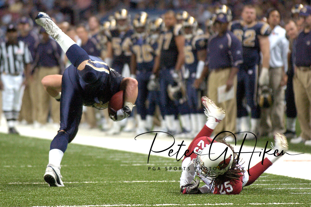 Arizona defensice back Eric Green (R) trips up St. Louis Rams running back Chris Massey (L) in the second half at the Edward Jones Dome in St. Louis, Missouri, November 20, 2005.  The Cardinals beat the Rams 38-28.