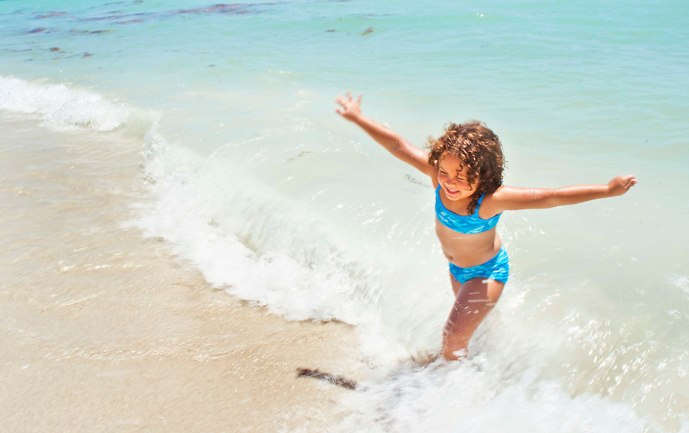 A young hispanic girl runs from the ocean waves on Miami Beach, FL.