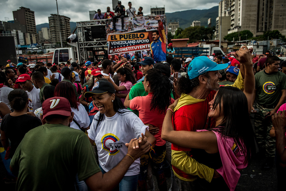 "CARACAS, VENEZUELA - JULY 27, 2017: Government supporters dance infront of a banner that says, in Spanish: ""The people of Venezuela support the Constituent"" as they celebrate the final campaign rally for candidates for the election of the new constituent assembly, that will be held on July 30th. They marched and danced in the streets, as President Maduro and other socialist leaders addressed the large crowd. Opponents of the government criticize President Maduro for calling for this election - saying the new assembly is a power grab, and will be a puppet of the President - the only candidates on the ballot are government loyalists. Critics also fear the new assembly will re-write the constitution and wipe out the democratically elected and opposition controlled congress. There have been widespread reports of voter intimidation, and of the government threatening state workers and citizens that receive government benefits like subsidized food - who report the government telling them they are obligated to vote, and if they don't, they will lose their jobs and benefits. Thousands have taken to the streets to protest the election in the days leading up to the July 30th vote.  PHOTO: Meridith Kohut for The New York Times"