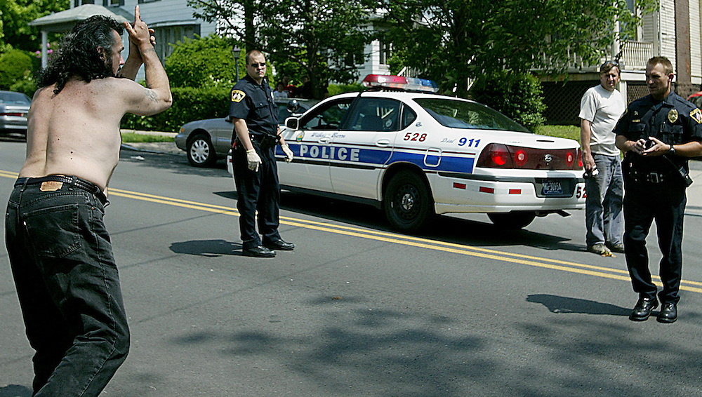 A man demonstrates to police what he witnessed during a broad daylight shooting on North Main Street in Wilkes Barre. Aimee Dilger/Photo TL 5/21/04 news