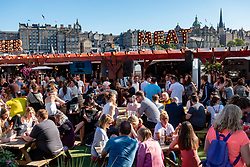 Busy outdoor bar in summer at Waverley Market shopping mall on Princes Street in Edinburgh, Scotland UK