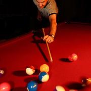 Chad Gardner shoots pool at his home in Bountiful, Utah November 10, 2005