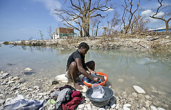 October 9, 2016 - HTI - Natalie Joseph cleans clothes in a river cutting through Roche a Bateau, Haiti on Sunday, Oct. 9, 2016. (Credit Image: © Patrick Farrell/TNS via ZUMA Wire)