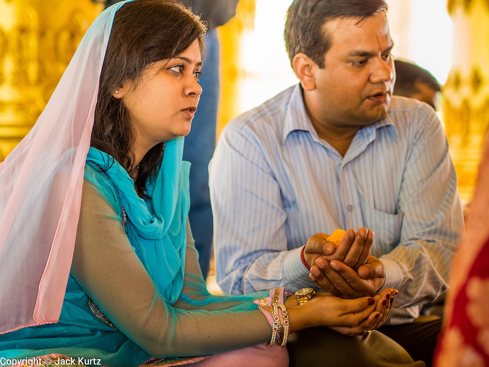 """09 SEPTEMBER 2013 - BANGKOK, THAILAND:  A couple at Shiva Temple in Bangkok holds a marigold during Ganesha Chaturthi celebrations at the temple. Ganesha Chaturthi also known as Vinayaka Chaturthi, is the Hindu festival celebrated on the day of the re-birth of Lord Ganesha, the son of Shiva and Parvati. The festival, also known as Ganeshotsav (""""Festival of Ganesha"""") is observed in the Hindu calendar month of Bhaadrapada. The date usually falls between 19 August and 20 September. The festival lasts for 10 days, ending on Anant Chaturdashi. Ganesha is a widely worshipped Hindu deity and is revered by many Thai Buddhists. Ganesha is widely revered as the remover of obstacles, the patron of arts and sciences and the deva of intellect and wisdom.    PHOTO BY JACK KURTZ"""