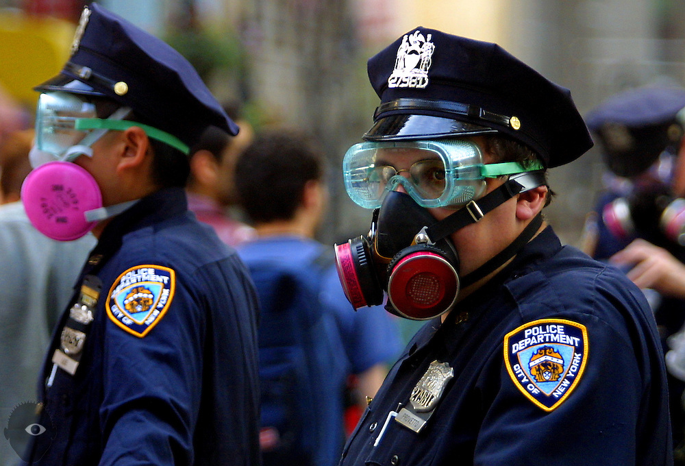 NYPD officers patrolling the area about Ground Zero wear goggles and breathing masks due to the heavy concentration of ash and other particulates about the site. Long exposure was shown to make some images ill.