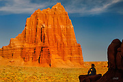 Sitting at the base of the Temple of the Moon, LB (age 8) gazes at sunrise reflecting off the 400-foot-tall Temple of the Sun in Cathedral Valley, Capital Reef National Park, Utah. The spectacular monolith is composed of Entrada Sandstone deposited 160 million years ago in the Jurassic period.  This fine-grained sandstone is formed by the deposition of silt in tidal flats. It crumbles easily to a fine sand which is rapidly removed by water, thus creating the sheer walls rising directly from their base. Seen two thirds of the way up the face, the Entrada sandstone is covered by a hard cap of grayish-green sandstone and siltstone of the Curtis Sandstone formation, protecting the monolith from erosion. Above the Curtis sandstone formation is the thinly-bedded, reddish-brown siltstone of the Summerville sandstone formation.