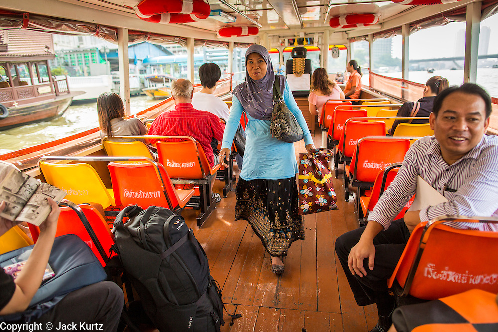 21 NOVEMBER 2012 - BANGKOK, THAILAND: A women walks down the aisle of a Chao Phraya Express boat. The Chao Phraya Express boats run up and down the Chao Phraya River in Bangkok providing a sort of bus service for neighborhoods near the river. The boats are the fastest way to get from north to south in Bangkok. Thousands of people commute to work daily on the Chao Phraya Express Boats and fast boats that ply Khlong Saen Saeb. Boats are used to haul commodities through the city to deep water ports for export.    PHOTO BY JACK KURTZ